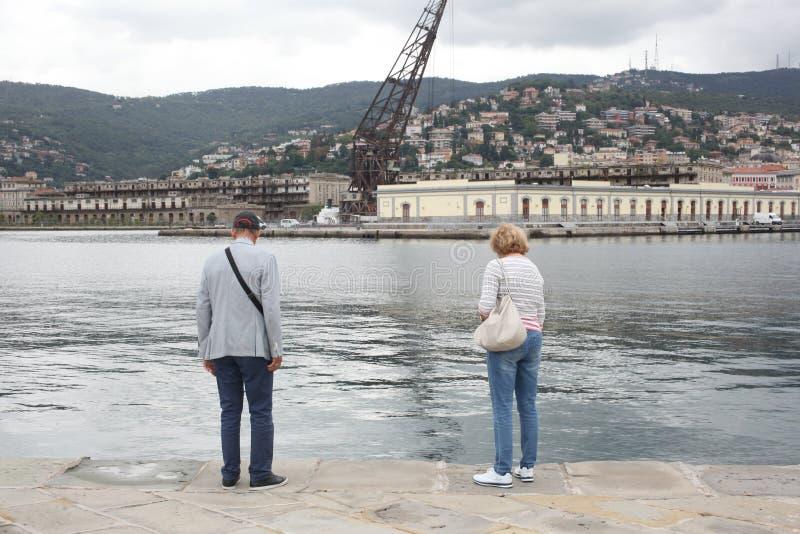 的里雅斯特, 2017年9月5日,意大利:站立在一个石码头的两个老年人看海 库存图片
