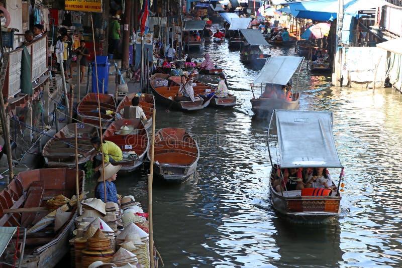 的长尾巴小船行服务游人和许多在运河的小船在Damnoen Saduak浮动市场上 免版税图库摄影