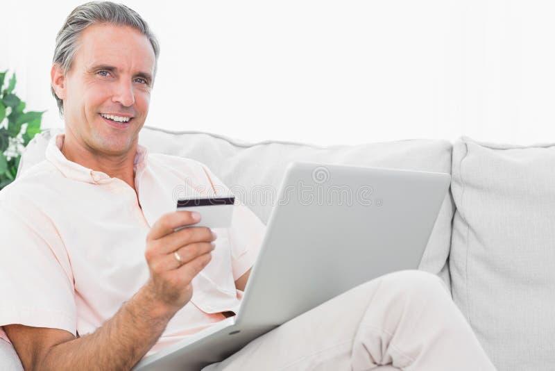 他的长沙发的愉快的人使用在网上购物的膝上型计算机 免版税库存图片