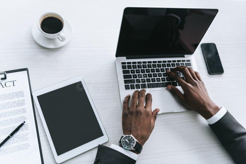 的非裔美国人的商人键入在膝上型计算机的部份观点在工作场所 库存图片