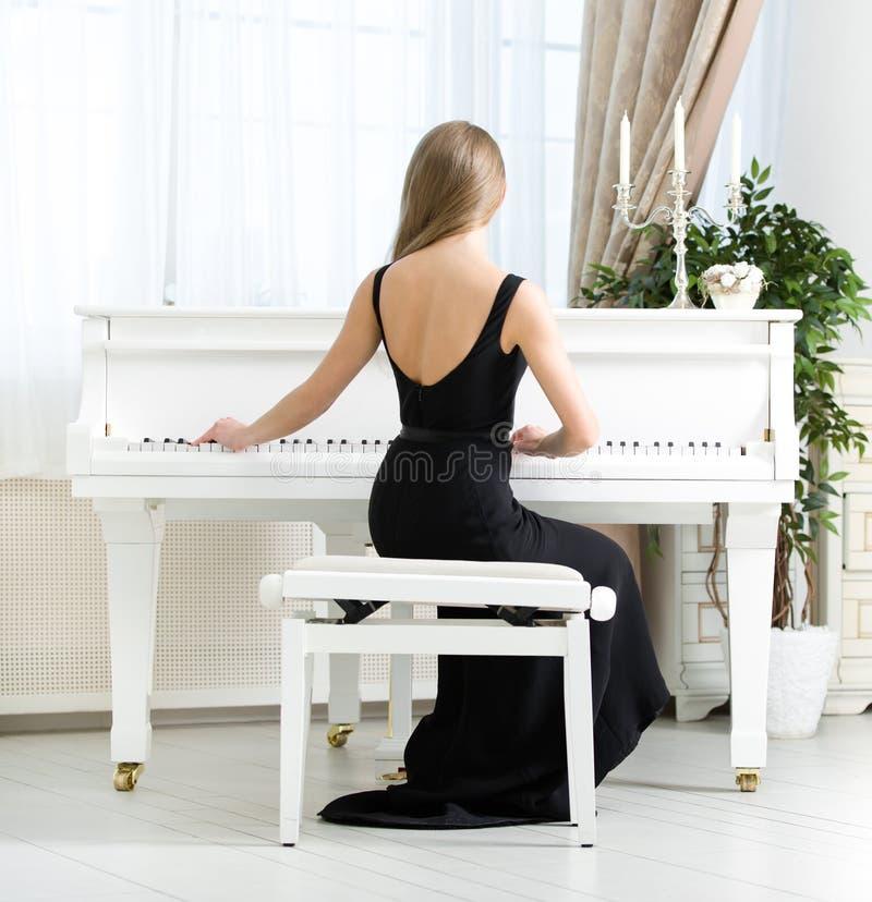 的音乐家坐和弹钢琴的后面观点 库存图片