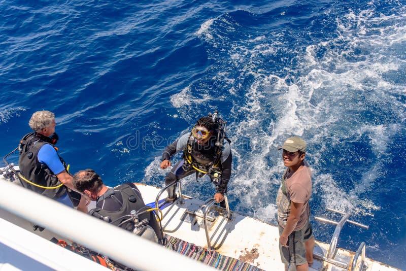 他的齿轮的轻潜水员在下潜小船 免版税图库摄影