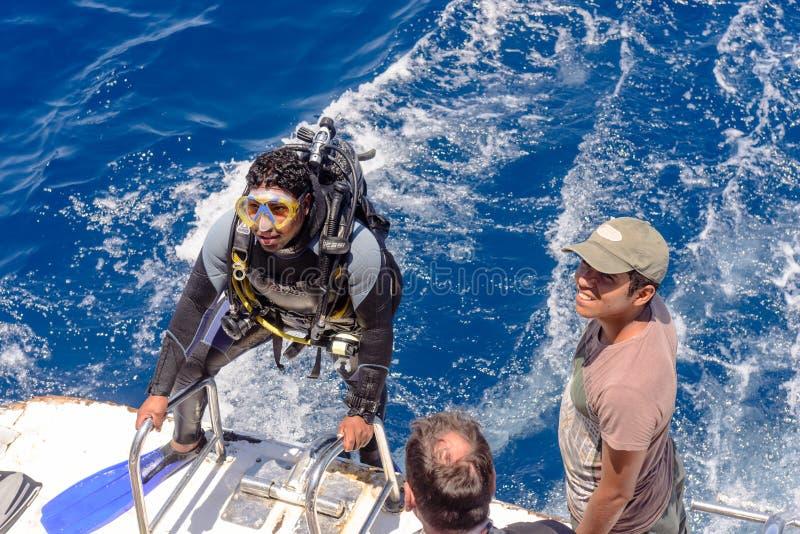 他的齿轮的轻潜水员在下潜小船 库存图片