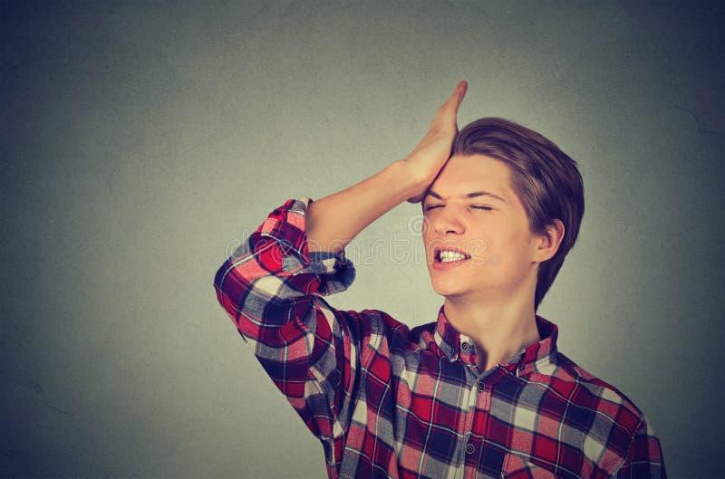 傻的年轻人,掴在有的头的手哈片刻 免版税图库摄影