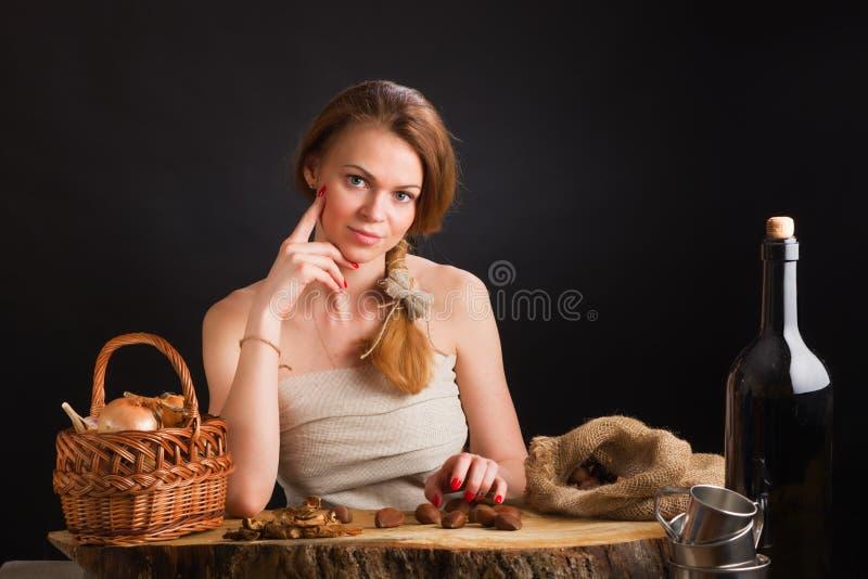 的年轻美丽的女孩从帆布的sundress坐在关于篮子的一张橡木桌上用葱和大蒜,干 库存照片