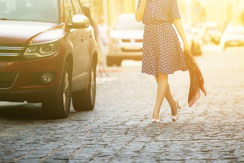 的年轻美丽的妇女蓝色sundress步行沿着向下街道的在汽车旁边,在他的手上拿着一件毛线衣 库存图片