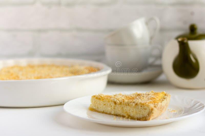 皇家乳酪蛋糕、可口新鲜的村庄奶酪蛋糕用一种油脂含量较高的酥饼和茶器物在桌上 免版税库存照片