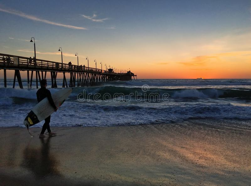 皇家海滩的冲浪者在圣地亚哥,加利福尼亚由惊人的日落点燃了 库存照片