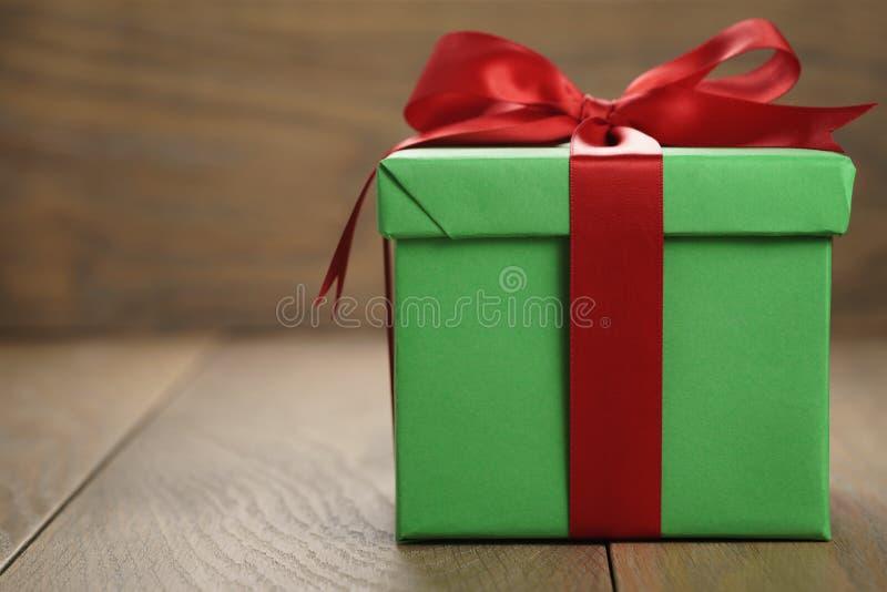 绿皮书礼物盒有盒盖的礼物盒和红色丝带在与拷贝空间的木桌上鞠躬 免版税库存图片