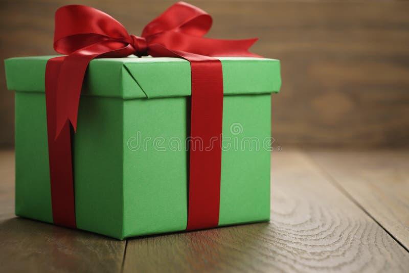 绿皮书礼物盒有盒盖的礼物盒和红色丝带在与拷贝空间的木桌上鞠躬 库存图片