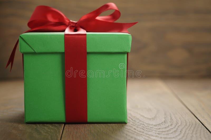 绿皮书礼物盒有盒盖的礼物盒和红色丝带在与拷贝空间的木桌上鞠躬 库存照片