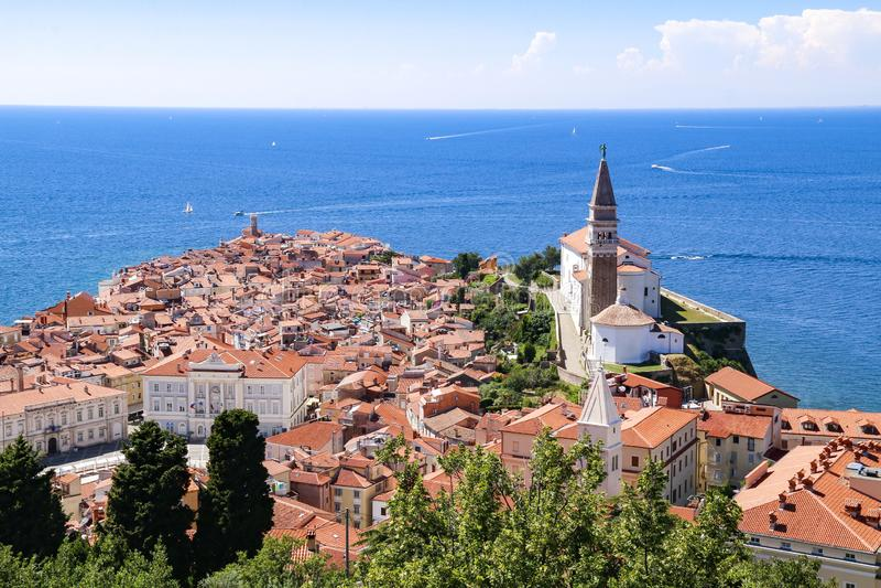 皮兰老镇的圣乔治的教会和红色铺磁砖的屋顶看法在斯洛文尼亚 免版税库存图片