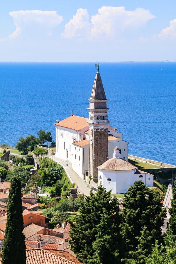 皮兰老镇的圣乔治的教会和红色铺磁砖的屋顶看法在斯洛文尼亚 库存图片