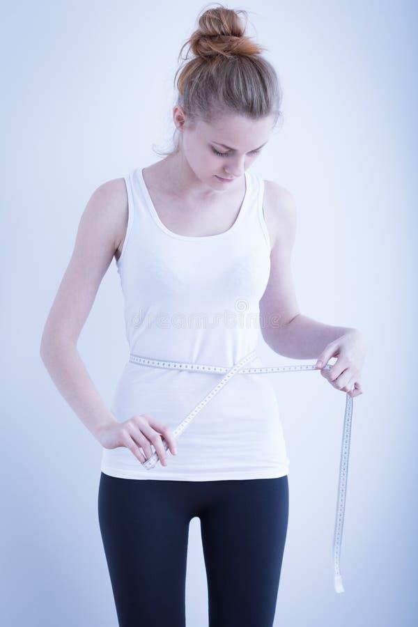 皮包骨头的女孩测量的腰部 免版税库存图片