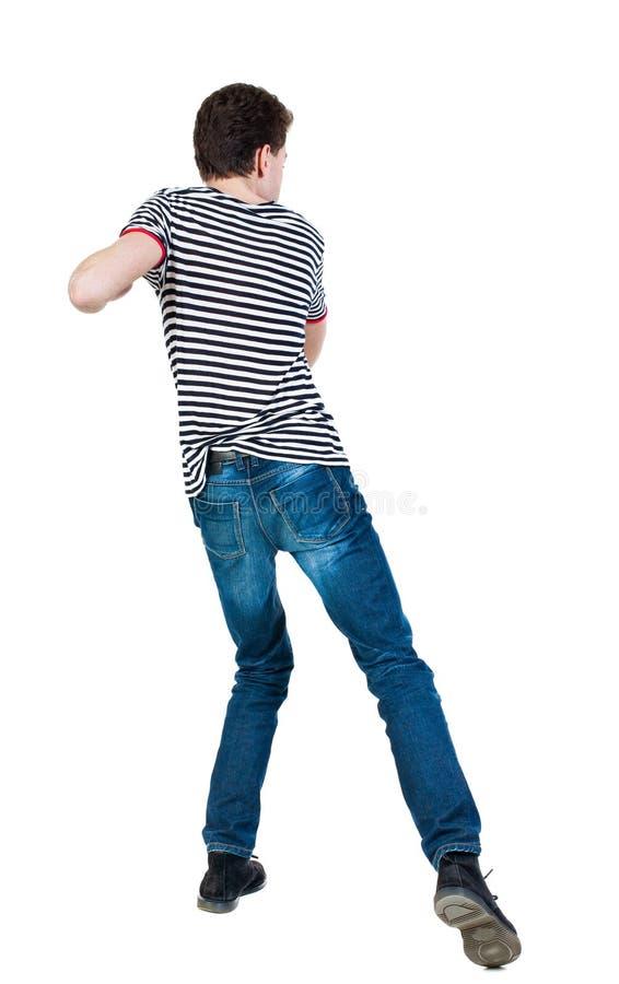 皮包骨头的挥动他的胳膊和腿的人滑稽的战斗后面看法  免版税库存图片