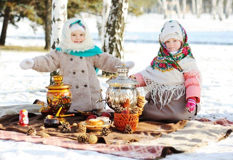 皮大衣和披肩的两个小女孩在他的俄国样式 库存图片