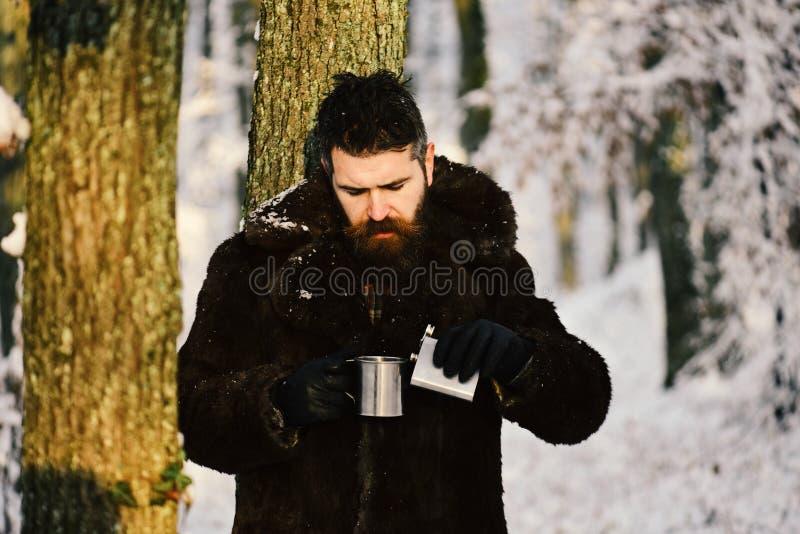 皮大衣的人拿着烧瓶和杯子 免版税库存照片