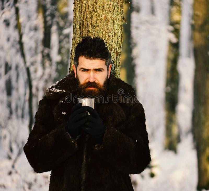 皮大衣的人拿着金属杯子 有胡子的强壮男子 免版税图库摄影