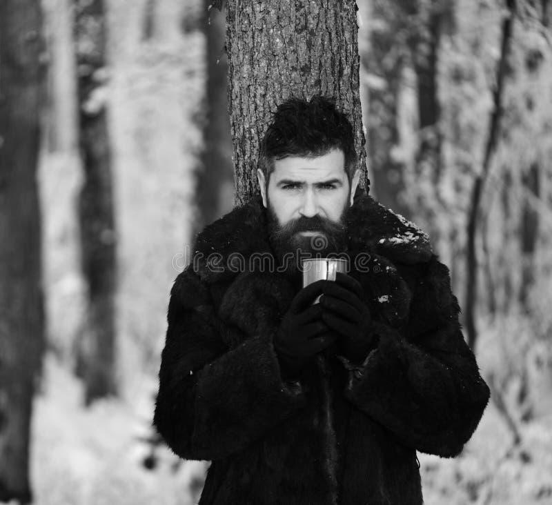 皮大衣的人拿着金属杯子 有胡子的强壮男子 库存照片