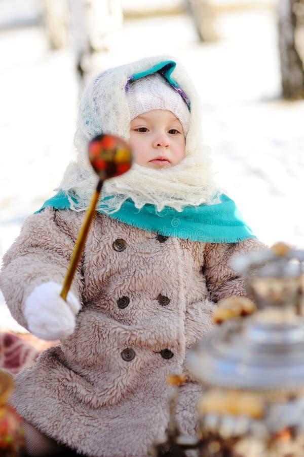 皮大衣的小女孩和在俄国样式w的一个头巾 免版税图库摄影