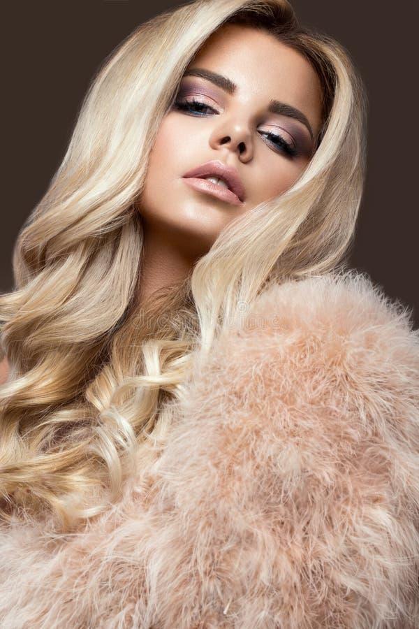 皮大衣的美丽的魅力blondie妇女,平衡构成和卷毛 面孔的秀丽 免版税库存照片