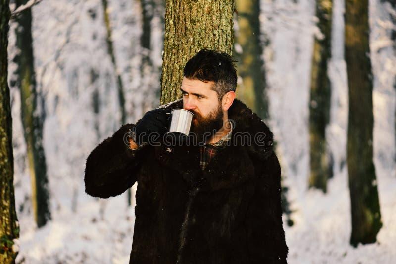 皮大衣饮料的人从金属杯子 免版税图库摄影