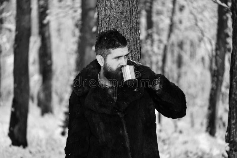 皮大衣饮料的人从金属杯子 图库摄影
