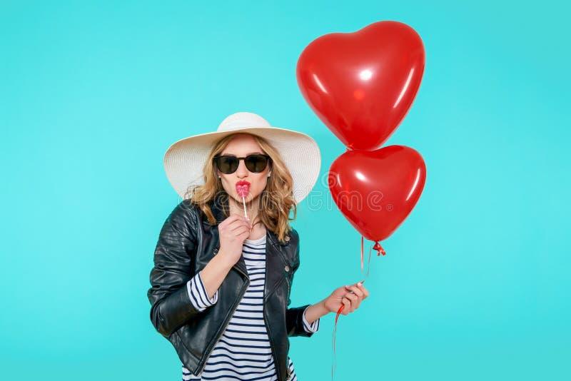 皮夹克和夏天帽子亲吻的心形的棒棒糖和拿着的心形的气球美丽的摇摆物女孩 免版税库存照片