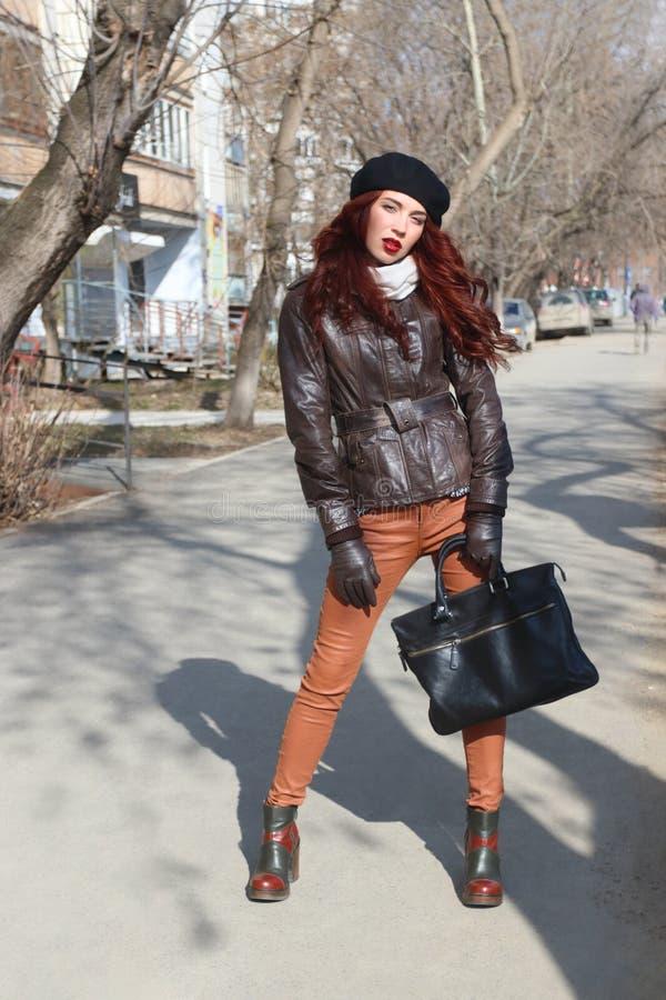 皮夹克和手套的女孩在街道上站立 免版税库存照片