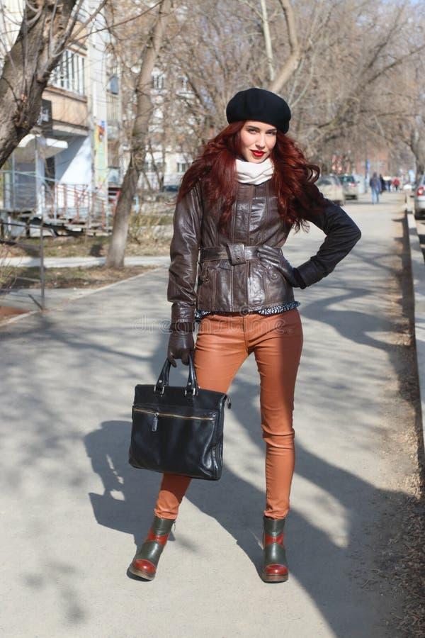 皮夹克和手套的愉快的女孩 免版税库存图片