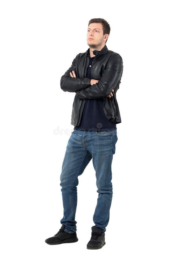 皮夹克和牛仔裤的严肃的年轻偶然人有看横渡的胳膊的  免版税库存图片