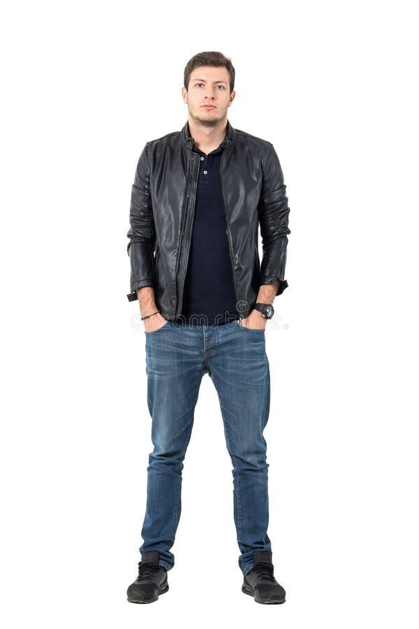 皮夹克和牛仔裤的确信的年轻偶然人用在口袋的手 库存图片