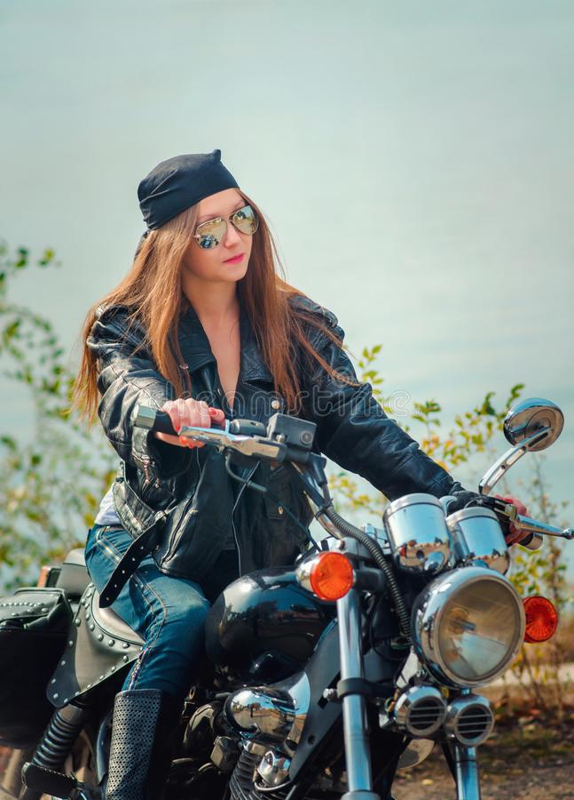 皮夹克和蓝色牛仔裤的美丽的少妇在g 免版税库存照片