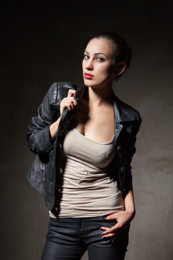 黑皮夹克和裤子的可爱的妇女 免版税库存照片