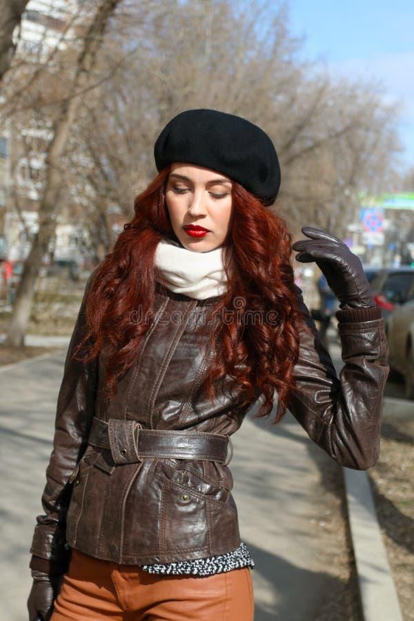 皮夹克姿势的美丽的妇女 免版税库存照片