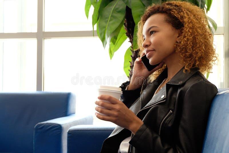 皮夹克的一个美丽的黑人女孩有一杯的咖啡谈话在电话,坐一个蓝色沙发在棕榈树ag附近 库存图片