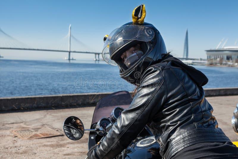 皮夹克的俏丽的骑自行车的人女孩和与面具的黑盔甲在回顾的面孔,当坐在摩托车时 免版税库存照片