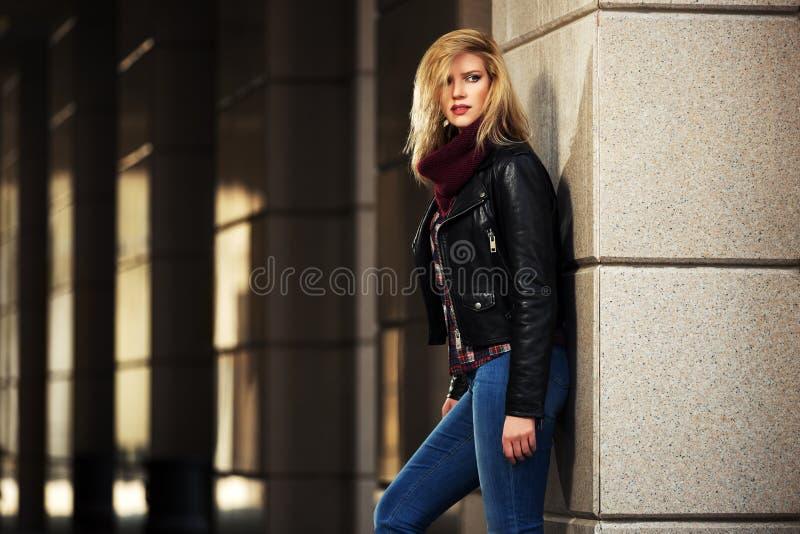 年轻皮夹克的时尚白肤金发的妇女在墙壁 免版税库存照片