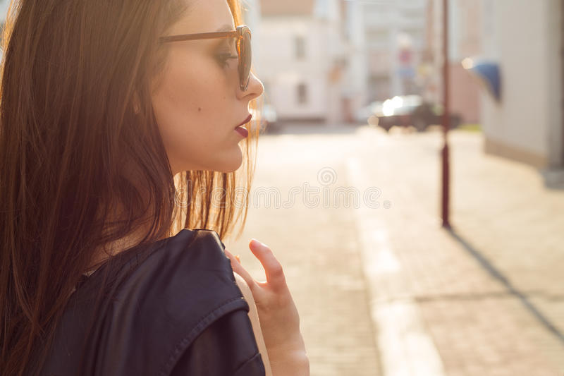 黑皮夹克的美丽的时髦的女孩有有一支黑暗的唇膏的太阳镜的在日落的城市 免版税库存照片