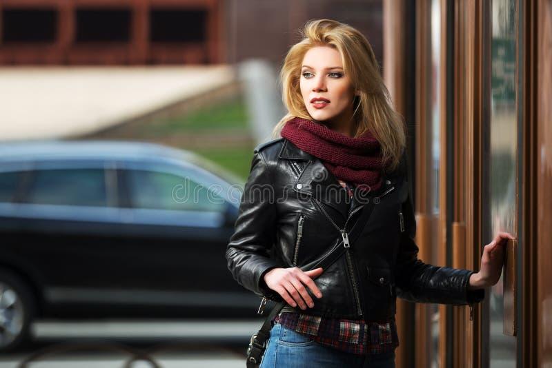 皮夹克的年轻时尚妇女在购物中心门 免版税库存图片