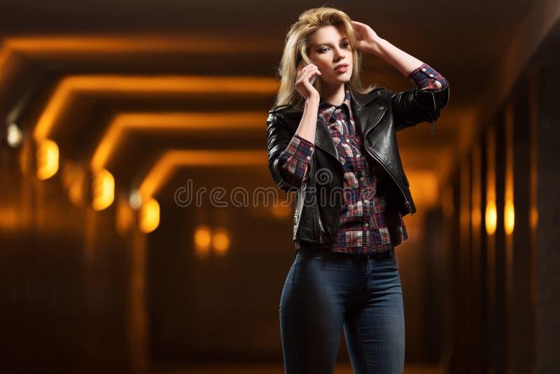 皮夹克的年轻时尚妇女拜访手机的 免版税库存照片