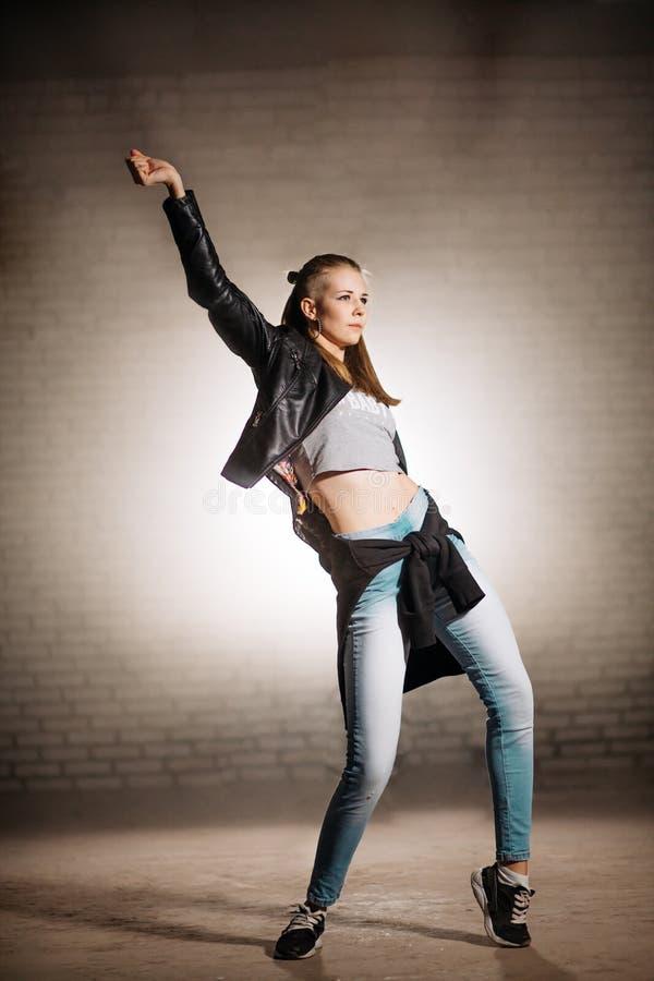 皮夹克跳舞的年轻女性在自由样式 库存图片