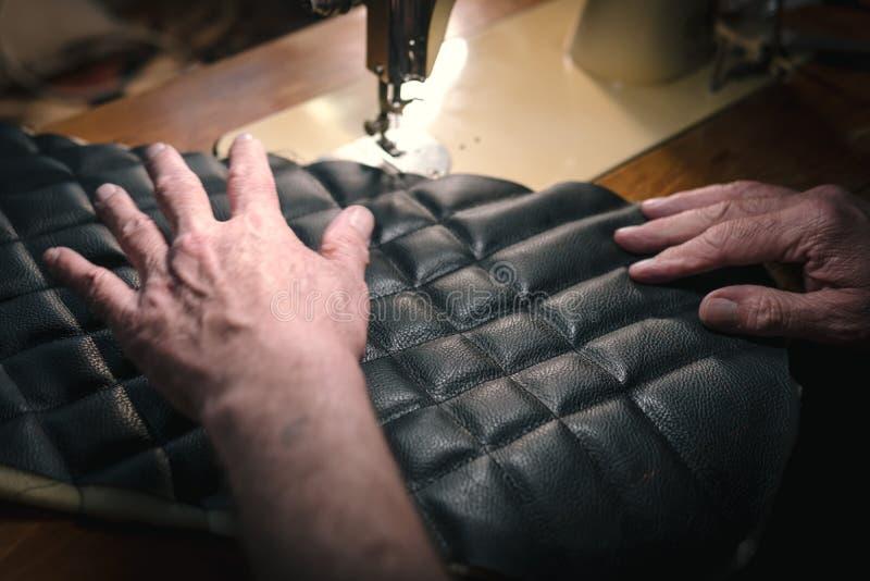 皮带的缝合的过程 在缝合后的老人的手 皮革车间 纺织品葡萄酒缝合工业 图库摄影