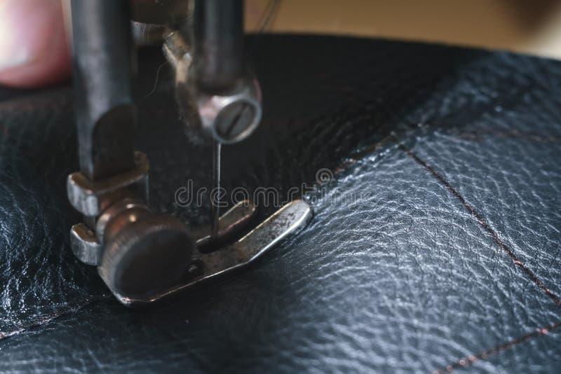 皮带的缝合的过程 在缝合后的老人的手 皮革车间 纺织品葡萄酒缝合工业 免版税库存图片