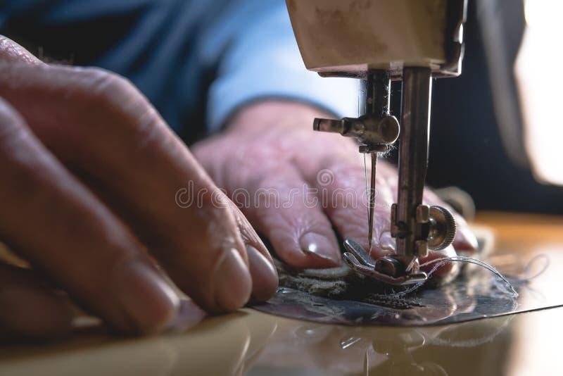 皮带的缝合的过程 在缝合后的老人的手 皮革车间 纺织品葡萄酒缝合工业 库存图片