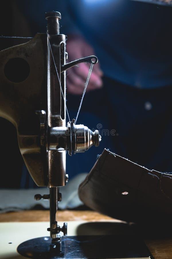 皮带的缝合的过程 在缝合后的老人的手 皮革车间 纺织品葡萄酒缝合工业 免版税库存照片