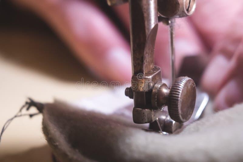 皮带的缝合的过程 在缝合后的老人的手 皮革车间 纺织品葡萄酒缝合工业 免版税图库摄影