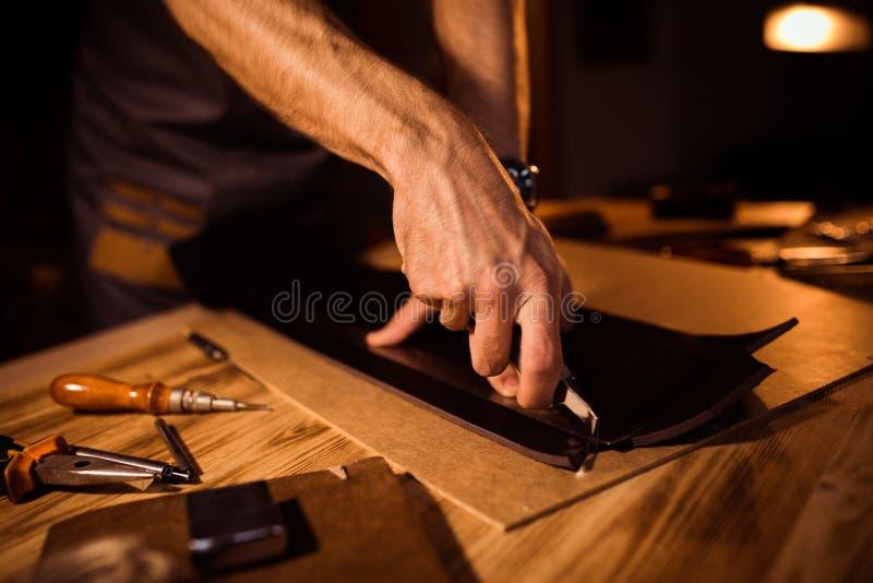 皮带的运作的过程在皮革车间 举行制作工具和工作的人 老的坦纳 图库摄影