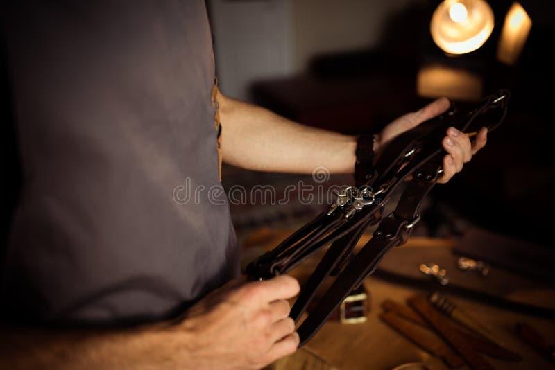 皮带的运作的过程在皮革车间 供以人员拿着摄影师照相机的` s传送带 在木的工具 图库摄影