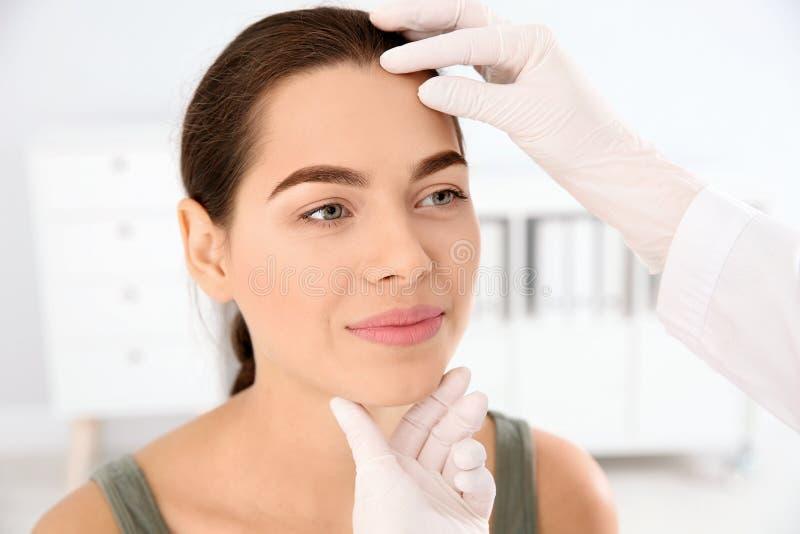 皮肤病学家在诊所的审查的患者的面孔 免版税库存照片